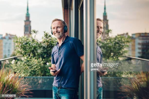gut aussehend bärtigen midaged mann genießen musik hören auf balkon - hobby stock-fotos und bilder