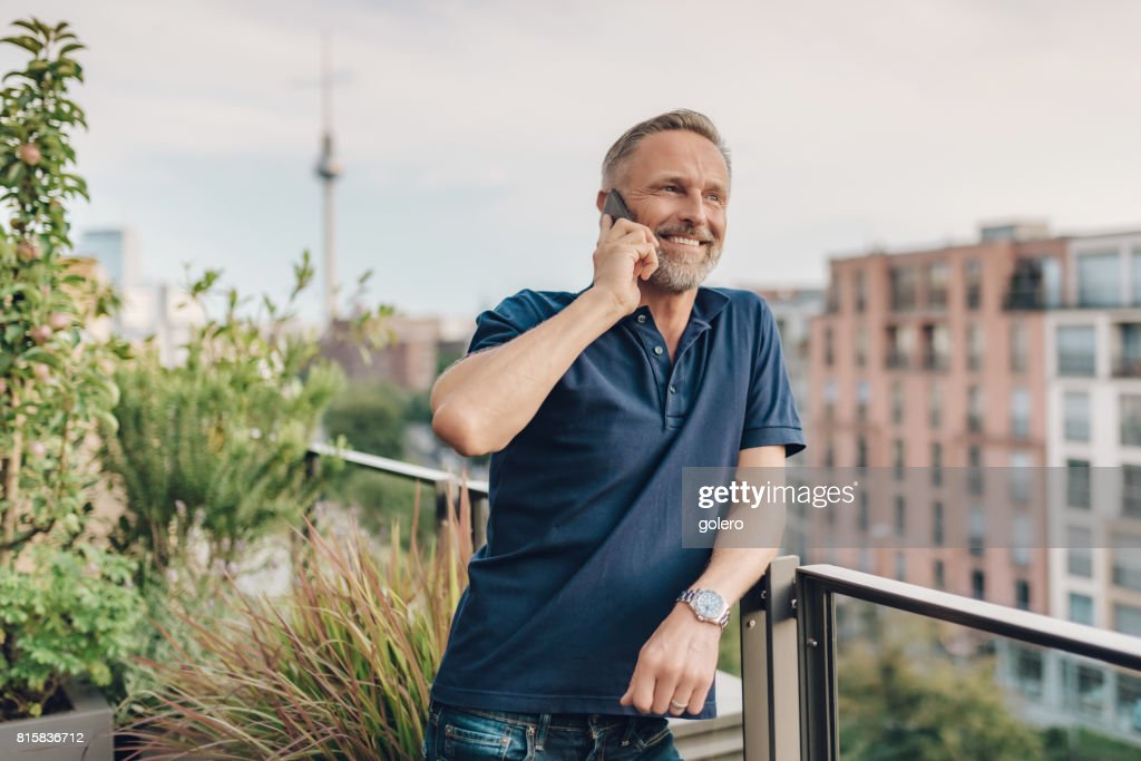handsome bearded midaged man talking on mobile at balcony in Berlin : Stock Photo