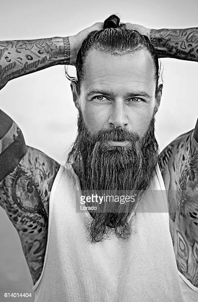Handsome bearded tattooed man posing for portrait