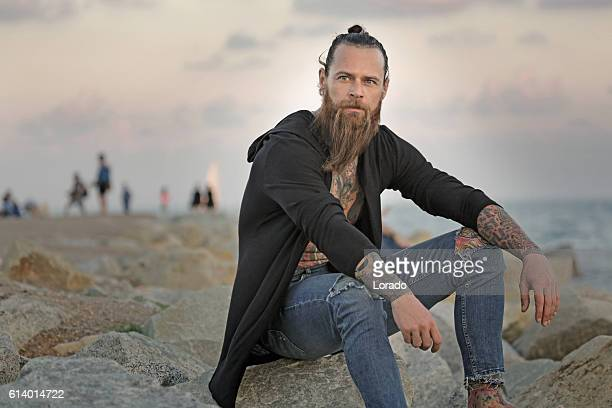 Handsome bearded tattooed man sitting alone by the sea