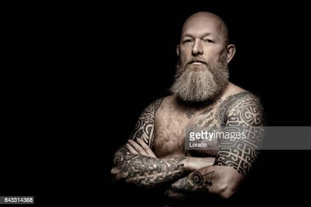 Stilig skäggiga tatuerade mellersta åldern man i studio shoot