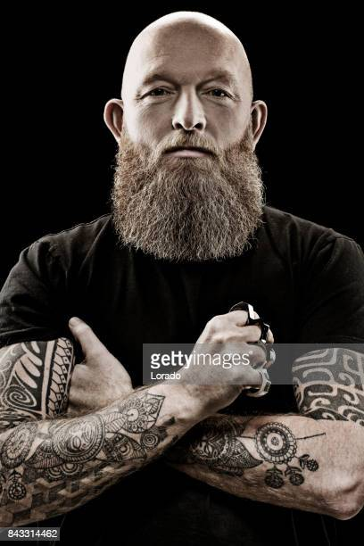 Handsome bearded tattooed middle aged man in studio shoot