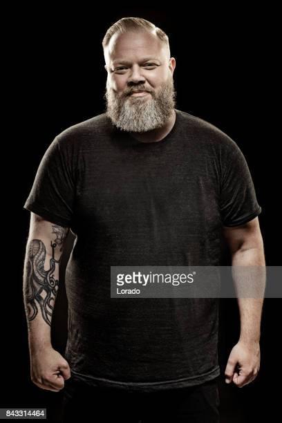 Knappe bebaarde getatoeëerd midden oude mens in studio shoot