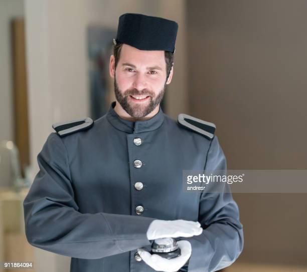 Knappe bellman in het hotel kijken camera glimlachen