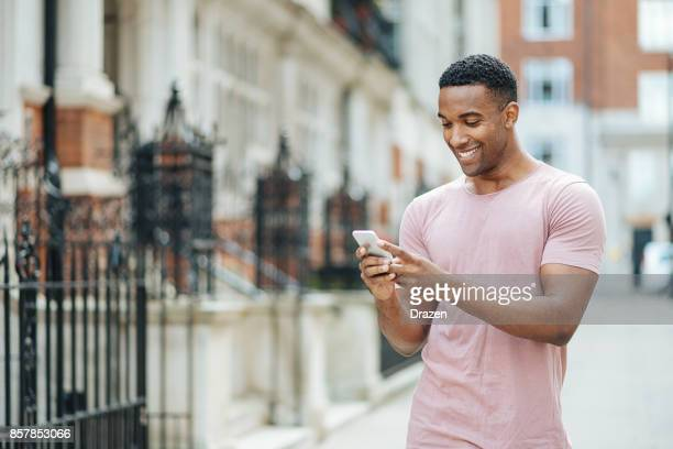 handsome black guy in london, using mobile phone - most handsome black men stock photos and pictures