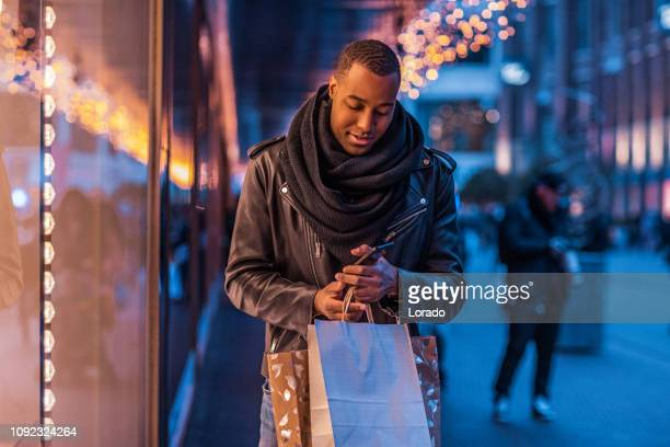 handsome black man at christmas shopping - december stock pictures, royalty-free photos & images