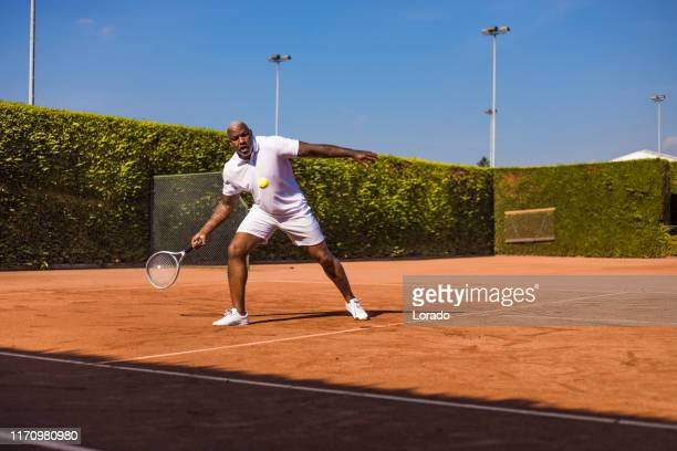 a handsome black middle aged male tennis player on the court - country club stock pictures, royalty-free photos & images