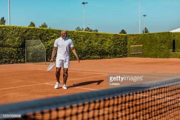 a handsome black middle aged male tennis player on the court - sports training drill stock pictures, royalty-free photos & images