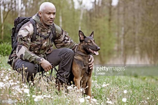犬と一緒に座っているハンサムな黒い中年男性 - 訓練犬 ストックフォトと画像