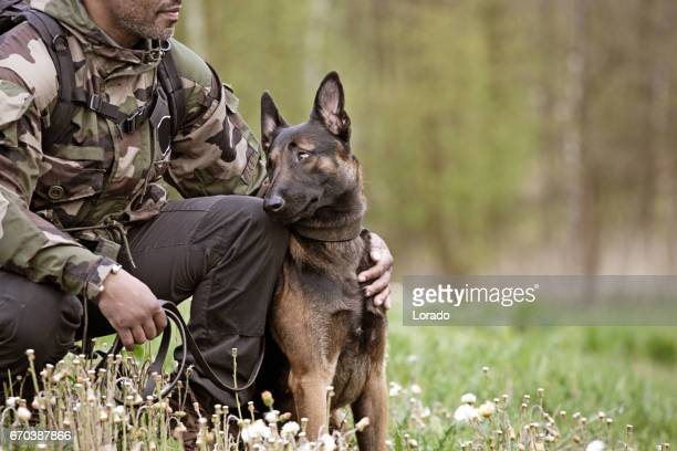 handsome black middle aged man sitting with dog - trained dog stock pictures, royalty-free photos & images