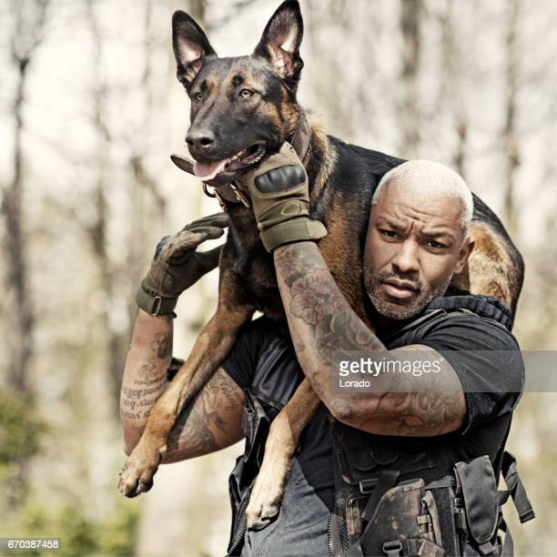 Handsome black middle aged man training with attack dog and trainer