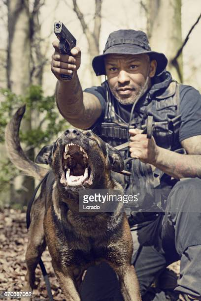 handsome black middle aged security agent working with guard dog in woodlands - guard dog stock photos and pictures