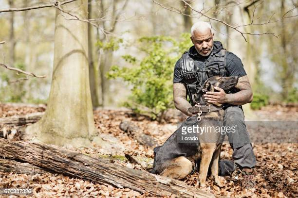 handsome black middle aged security agent working with guard dog in woodlands - trained dog stock pictures, royalty-free photos & images