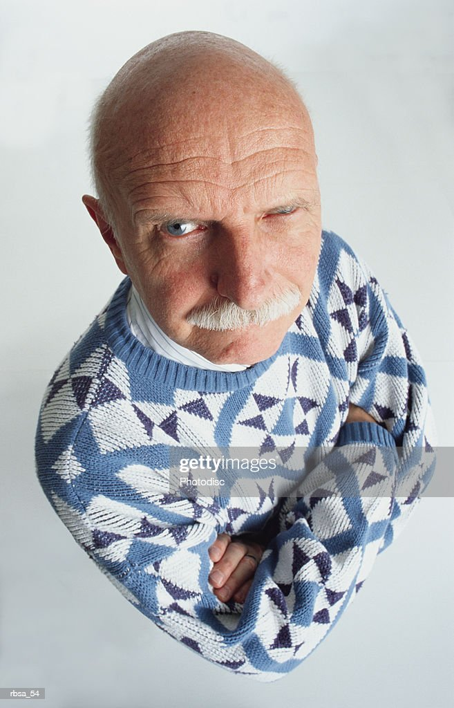 handsome blue eyed old bald caucasian adult male with a moustache wearing a blue and white patterned sweater stands with arms folded looking up at the camera with one eye staring and an accusative expression on his face : Stockfoto