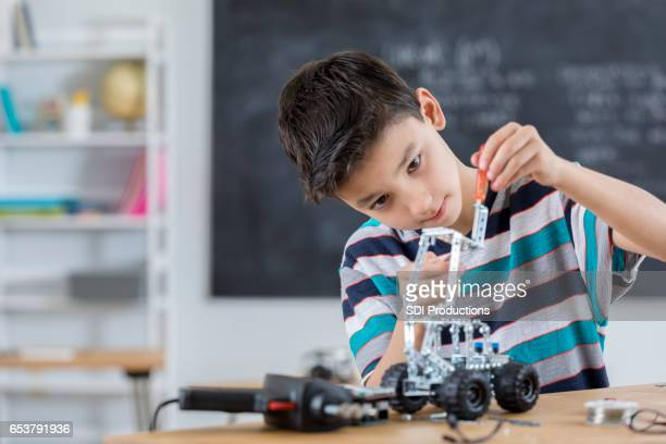 Handsome boy builds robot at school