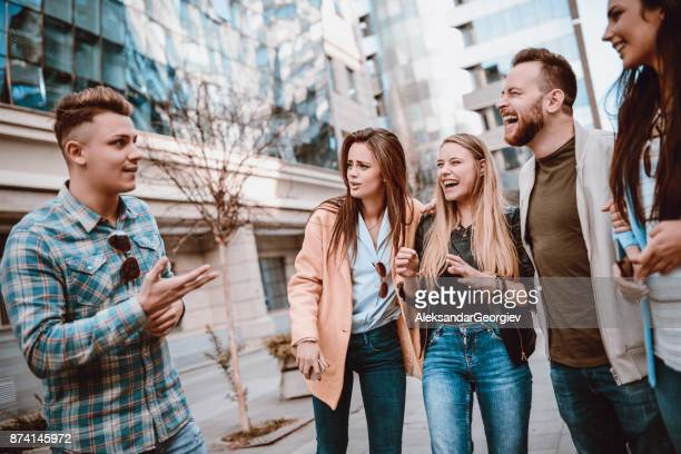 handsome boy telling a joke and group of friends laughing in tears - storytelling stock pictures, royalty-free photos & images
