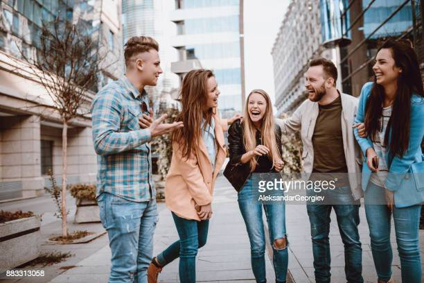 handsome boy telling a joke and group of friends laughing in tears - storyteller stock pictures, royalty-free photos & images