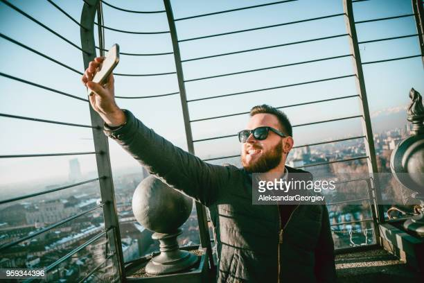 Beau garçon avec des lunettes de soleil prenant Selfie au bel endroit à Turin