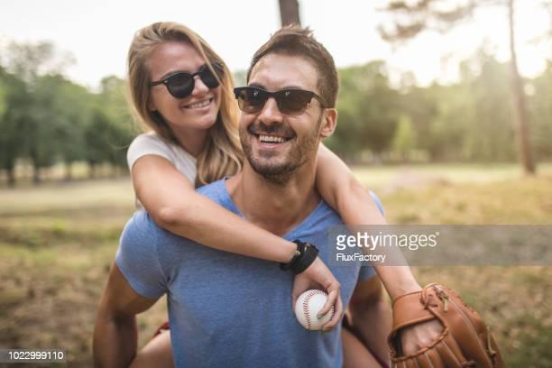 Beau petit ami porter sa petite amie sur son dos dans un parc