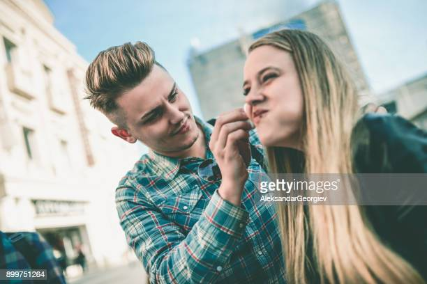 handsome boyfriend cleaning smiling girlfriend's nose from chocolate - couple chocolate stock pictures, royalty-free photos & images