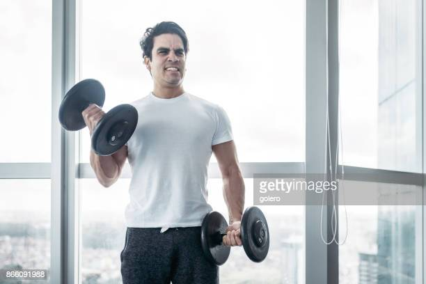 handsome brazilian sportsman lifting dumbells in fitness room - durability stock photos and pictures