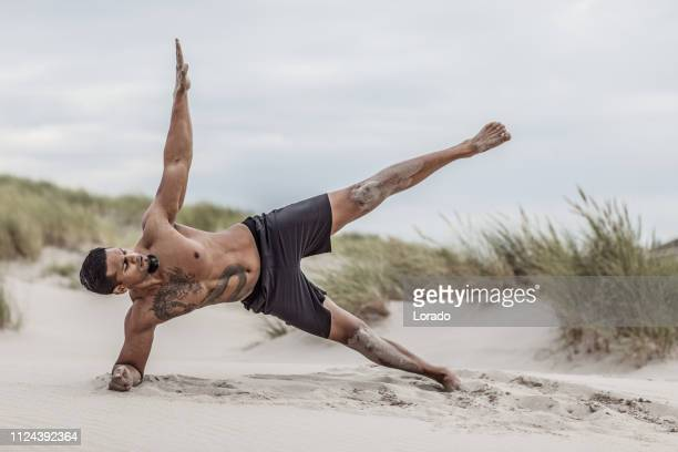 handsome brunette man during workout - muscle men at beach stock photos and pictures