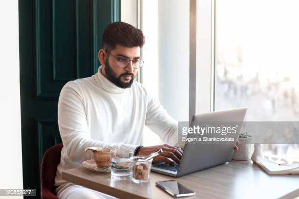 handsome businesman sitting in cafe and working. - male likeness stock pictures, royalty-free photos & images