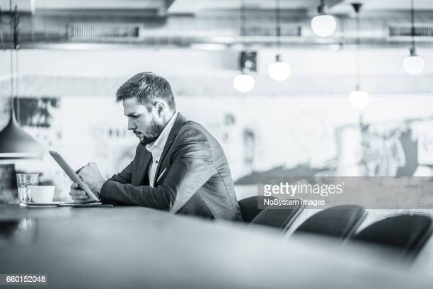 Handsome business man, sitting in a bar, drinking coffee,  browsing tablet, reading news, writting down something. Some grain added