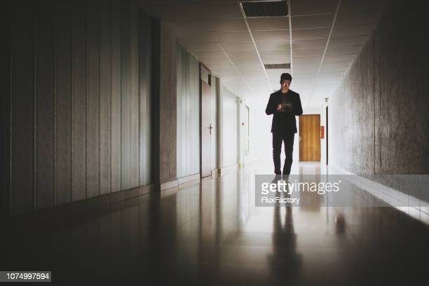 handsome business person walking while looking at a digital tablet - entrance hall stock pictures, royalty-free photos & images