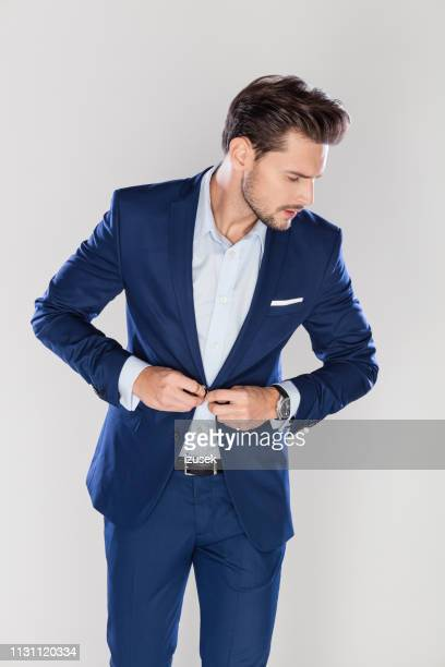 handsome businessman buttoning his jacket - blazer jacket stock pictures, royalty-free photos & images