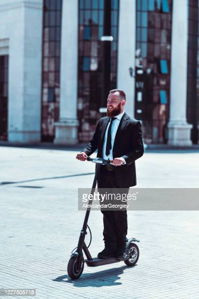 handsome businessman enjoying electric scooter as transport to work - electric scooter stock pictures, royalty-free photos & images