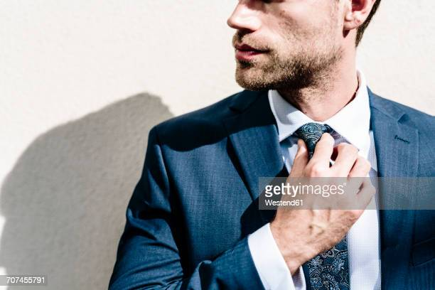 Handsome businessman fixing his tie, standing in front of white wall