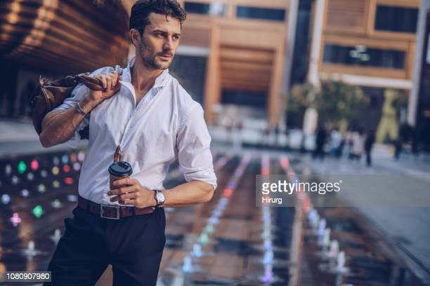 handsome businessman having takeaway coffee - suave stock pictures, royalty-free photos & images