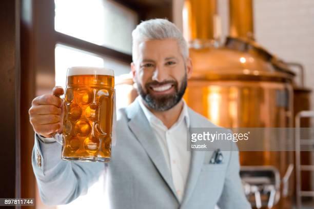 handsome businessman holding a beer mug at brewery - izusek imagens e fotografias de stock