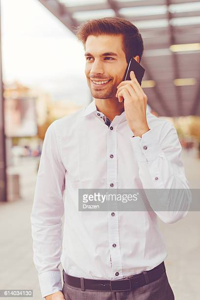 handsome businessman in white shirt discussing investments - only young men stock pictures, royalty-free photos & images