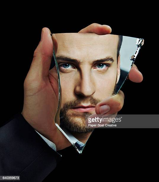 Handsome businessman looking in broken glass