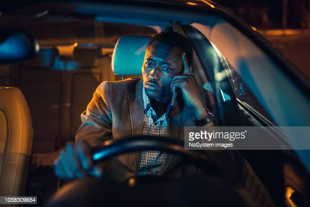 handsome businessman on a business trip, driving at night. african ethnicity - tired stock pictures, royalty-free photos & images
