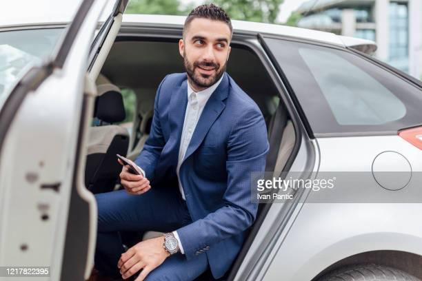 車に乗ってハンサムなビジネスマン - 降り立つ ストックフォトと画像