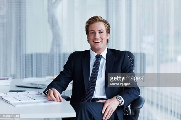 handsome businessman sitting at desk - kompletter anzug stock-fotos und bilder