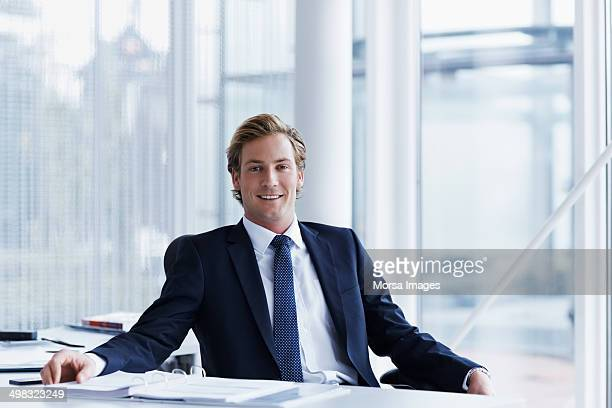 handsome businessman sitting at desk - geschäftsmann stock-fotos und bilder
