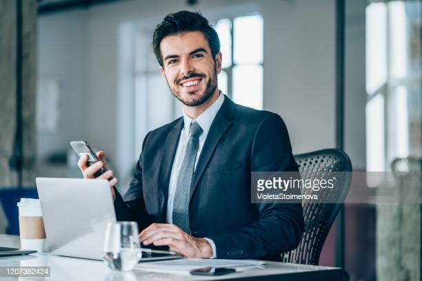 handsome businessman sitting in modern office. - businessman stock pictures, royalty-free photos & images