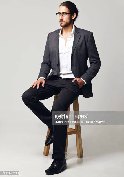 Handsome Businessman Sitting On Stool Against White Background