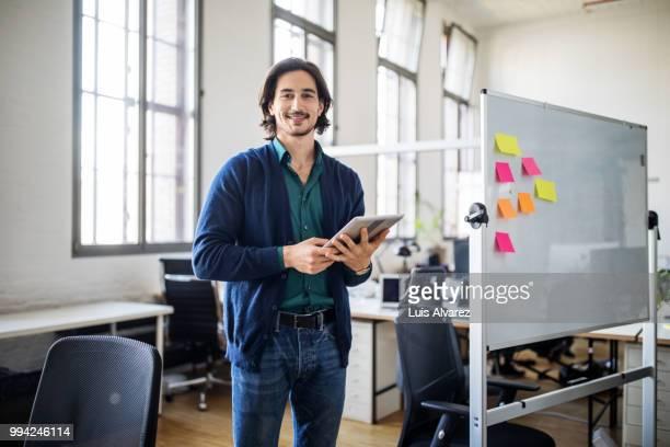 handsome businessman standing with digital tablet - utilizar o tablet - fotografias e filmes do acervo