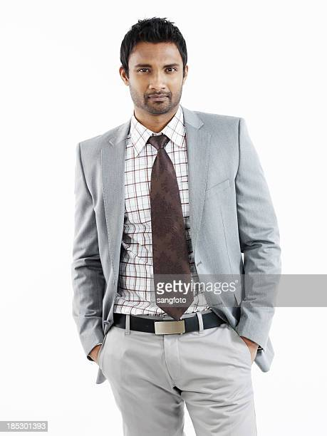 Handsome businessman standing with hands in pockets
