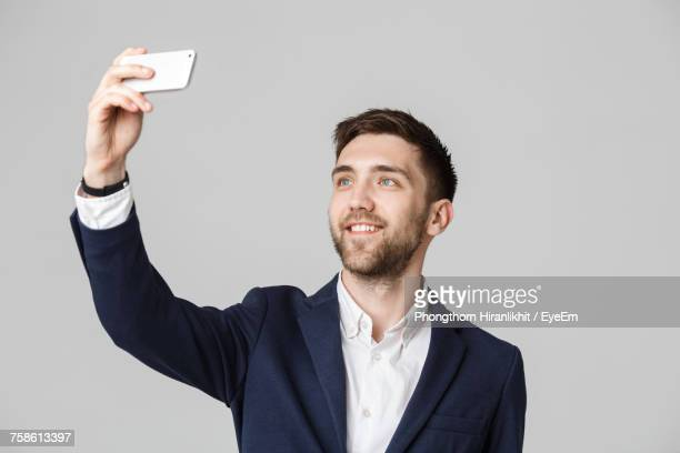Handsome Businessman Taking Selfie Against Gray Background