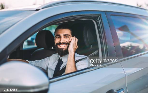 Handsome businessman talking on the phone while waiting in the car