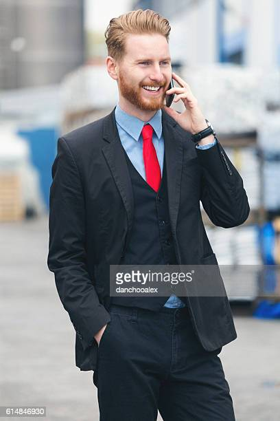 Handsome businessman talking on the smart phone at warehouse