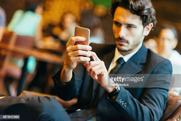 handsome businessman typing text message