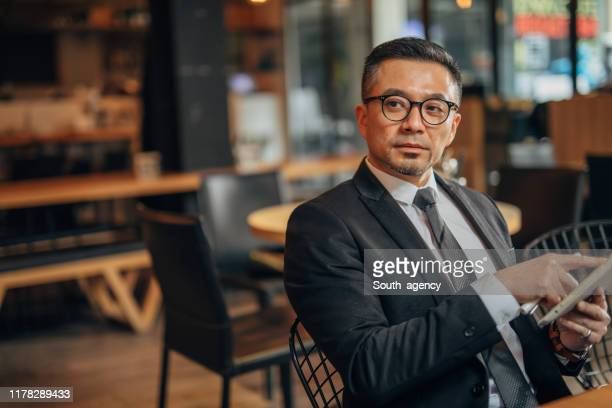 handsome businessman using digital tablet in restaurant - chinese ethnicity stock pictures, royalty-free photos & images