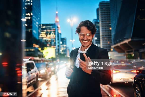 homem de negócios considerável que usa seu smartphone na cidade - a caminho - fotografias e filmes do acervo